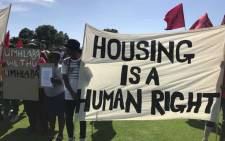 FILE: Reclaim the City supporters hold placards during a protest for land to build houses at the Rondebosch Golf Course in Cape Town on 22 March 2019. Picture: @UniteBehind/Twitter