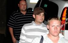 Two of the 'Waterkloof Four' Reinach Tiedt, front, and Frikkie du Preez, 2nd from front, are escourted by a police officer to a car to take them to prison to begin their 12-year sentence for murder and assault on Monday, 11 August 2008 in Pretoria. Tiedt, Du Preez, Gert van Schalkwyk (also present but not in picture) and Christoff Becker (in Cape Town) were sentenced to 12 years imprisonment for murdering an unknown man and assaulting another in a park in 2001 while they were at school. Picture: Trevor Kolk/SAPA