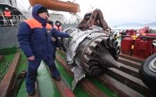 This handout shows rescuers looking at fragments of the engine and the landing gear of the crashed Tu-154 military plane after lifting it during searches in the underwater area outside Sochi, in the Black Sea. Picture: AFP/Russian Emergency Ministry.
