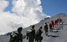 Japanese soldiers and rescue workers searching for missing people after a volcano erupted on 28 September 2014. Picture: AFP.