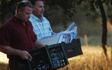 Investigators carry files gathered from Nico Henning's properties on 3 October, 2012. Picture: Barry Bateman/EWN.