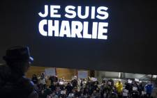 "People hold signs with words reading ""Je Suis Charlie"" (I Am Charlie) beneath an electronic display echoing the sentiment outside the Newseum 7 January, 2015 in Washington. Picture: AFP"