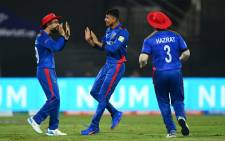 Afghanistan spinner  Spinner Mujeeb Ur Rahman (centre) celebrates a wicket with teammates during their ICC T20 World Cup match against Scotland on 25 October 2021. Picture: @T20WorldCup/Twitter