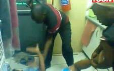 A screengrab from an exclusive Daily Sun video which shows an elderly woman being beaten with a rubber hammer.