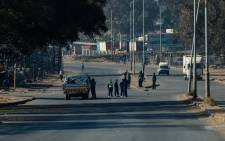 Zimbabwe police ask for travel documents at a road block in Harare 31 July 2020 where they were deployed following a ban on anti-government protests planned for the same day by Zimbabwe opposition political leader Jacob Ngarivhume who has since been detained in custody pending an application for bail. Picture: AFP