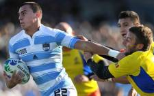 Argentina's Juan Jose Imhoff (L) runs to score a try ahead of Romania's scrum-half Florin Surugiu during a 2011 Rugby World Cup pool B match. Picture: AFP.