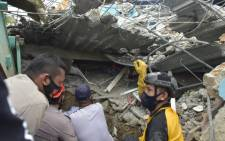 Rescuers search for survivors at the Mitra Manakarra hospital in Mamuju city on  15 January 2021, where patients and staff were trapped beneath the rubble after the hospital was flattened when a 6.2-magnitude earthquake rocked Indonesia's Sulawesi island. Picture: Firdaus/AFP.