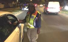 A JMPD official checks a driver's licence card during a police festive season operation on 20 December 2019. Picture: @WayneMinnaar2/Twitter