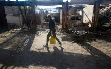 A woman carries a buckets of water through the yard of a destroyed hospital following shelling in the town of Popasna of Lugansk region on 1 October, 2014. Picture: AFP.