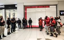 Public safety officers and police watch EFF members protest outside a Clicks store at the Sandton City shopping centre in Johannesburg on 7 September 2020. Picture: Kayleen Morgan/EWN