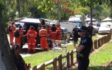 This photo shows the police (R) at the scene outside a house where eight children ranging from babies to teenagers were found dead in the northern Australian city of Cairns on 19 December, 2014. Picture: AFP.