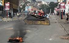 A few hundred people gather in the centre of Antananarivo on 22 April 2018 to erect a roadblock, during a rally to protest against the new electoral laws. The demonstrators are protesting against new electoral laws that the opposition claim could stop some candidates from standing in the upcoming presidential elections of November or December 2018. Picture: AFP.