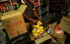 An Indian shopkeeper puts packs of Nestle Maggi instant noodles into a plastic bag in his shop in New Delhi after it was recalled over a health scare. Picture: AFP.