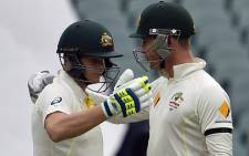 Australia's batsman Steve Smith (L) hugs team captain Michael Clarke as he reaches his century during the second day of the first Test cricket match between Australia and India at the Adelaide Oval on 10 December, 2014. Picture: AFP.