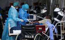 Professional healthcare workers wearing personal protective equipment (PPE) attend to a patient inside the temporary ward dedicated to the treatment of possible COVID-19 coronavirus patients at Steve Biko Academic Hospital in Pretoria on 11 January 2021. Picture: Phill Magakoe/AFP