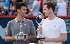 Novak Djokovic of Serbia and Andy Murray of Great Britain looks at one another as they hold their trophies during day seven of the Rogers Cup at Uniprix Stadium on 16 August, 2015 in Montreal, Quebec, Canada. Picture: AFP.
