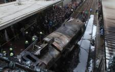 Firefighters and onlookers gather at the scene of a fiery train crash at the Egyptian capital Cairo's main railway station on 27 February 2019. Picture: AFP