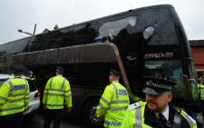The bus carrying the Manchester United team is escorted by police after having a window smashed on its way to West Hams Boleyn ground before the English Premier League football match between West Ham United and Manchester United in in east London on 10 May, 2016. Picture: AFP.
