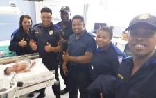 Officers are seen with the newborn baby girl at the Mitchells Plain day hospital. Picture: Supplied.