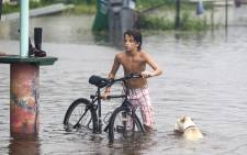A young man and his dog wades in the storm surge from Hurricane Hermaine outside Cooter Stew Cafe on 1 September 2016 in Saint Marks, Florida. Picture: Getty Images North America/AFP.