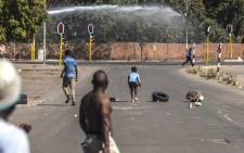A man runs to cover from a police water cannon during during a demonstration on 6 July 2016 in Bulawayo in Zimbabwe. Picture: AFP.