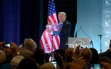 A screengrab of US President Donald Trump hugging his country's flag at an event. Picture: CNN