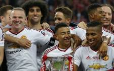 Manchester United's English midfielder Jesse Lingard, (Front C) Manchester United's French striker Anthony Martial (Below R)and Manchester United's English striker Wayne Rooney (Top L) celebrate in London on 21 May 2016. Picture: Ian Kington/AFP.