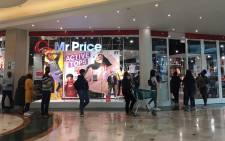 There is a long queue outside Mr. Price than other clothing outlets at Canal Walk. People are social distancing and hands are sanitised before entering. Picture: Jarita Kassen/EWN