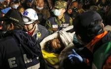 Rescuers carry a survivor who is trapped from a collapsed building following a 6.4 magnitude earthquake struck the area in Tainan City, southern Taiwan, 7 February 2016. Picture: EPA/RITCHIE B. TONGO