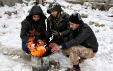 Rebel fighters heat themselves by a fire after snow falls in the rebel-held side of the Syrian northern city of Aleppo. Picture: AFP.