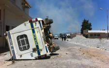 FILE. A police vehicle overturned during violent farm protests in Wolseley. Picture: EWN