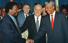 FILE: South African President Frederik W. De Klerk (centre) smiles while ANC leader Nelson Mandela (right) and IFP leader Mangosuthu Buthelezi shake hands after they signed an agreement at the Union Buildings in Pretoria 19 April 1994. Pik Botha, South African Foreign Affairs Minister (C, 2nd row) looks on. Picture: AFP.