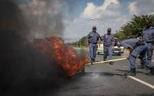 FILE: Police clear a burning tyre off The Golden Highway, set alight by protesters in Eldorado Park and Freedom Park who are protesting over service delivery. Picture: Thomas Holder/EWN