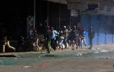 "People run as riot police use tear gas and water cannons while patrolling the streets to break up barricades set up by the opposition led by the Movement for Democratic Change (MDC) during protests over ""uneven"" distribution of voter registration centres for Zimbabwe 2018 general elections on 12 July 2017 in Harare. Picture: AFP."