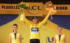Great Britains Christopher Froome celebrates his overall leader yellow jersey on the podium at the end of the 28 km team time-trial, the ninth stage of the 102nd edition of the Tour de France cycling race on 12 July, 2015, between Vannes and Plumelec, western France. Picture: AFP.