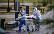 Medics escort a woman into a hospital where patients infected with the COVID-19 novel coronavirus are being treated in the settlement of Kommunarka outside Moscow, Russia, on 30 June 2021. Picture: Dimitar DILKOFF/AFP