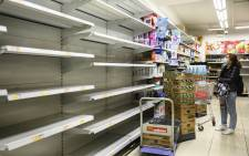 A woman wearing a facemask as a preventative measure following a coronavirus outbreak which began in the Chinese city of Wuhan, looks at empty supermarket shelves, which were used to stock paper towels, in Hong Kong on 5 February 2020. Picture: AFP
