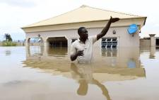 A man gestures next to his flooded house following heavy rain near the Nigerian town of Lokoja in Kogi State on 14 September 2018. Picture: AFP