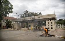 A trolley filled with plastic dustbins burns just inside the University of Fort Hare's gates as some students watch from the side. Picture: Thomas Holder/EWN