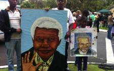 Artists hold up Nelson Mandela's protrait outside his home in Houghton on 6 December 2013. Picture: Sebabatso Mosamo/EWN.