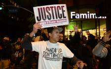 FILE: A group of protesters demonstrate in downtown Los Angeles, California on 26 November 2014 after a controversial verdict in the police shooting case in Ferguson, Missouri. Picture: EPA.