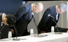 Tadashi Ishii (C), president of Japan's biggest advertising agency Dentsu, bowing with other executives during a press conference in Tokyo. Picture: STR/Jiji Press/AFP.