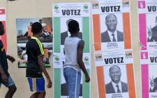 Boys walk past Ivory Coasts presidential election candidates campaign posters on October 14, 2015 in Cocody Abidjan.  Picture: AFP.