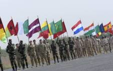Soldiers carry national flags during the inauguration of a military base in Thies, 70 km from Dakar, on on the second day of a three-week joint military exercise between African, US and European troops, known as Flintlock. Picture: Seyllou/AFP.