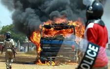 Armed Zambian police officers stand near a burning truck in Lusaka's Kanyama area during election riots. AFP