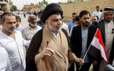 Iraqi Shiite cleric and leader Moqtada al-Sadr (C-L) shows his ink-stained index finger and holds a national flag while surrounded by people outside a polling station in the central holy city of Najaf on 12 May 2018. Picture: AFP