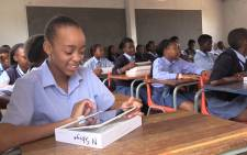 FILE: A Gauteng pupil smiles as she inspects her new tablet. Picture: EWN.