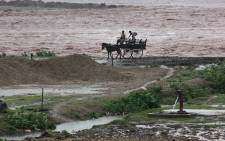 FILE: Indian villagers transport their belongings on a horse cart as they head for higher ground during a flash flood on the banks of the River Tawi in Jammu on 4 September, 2014. Picture: AFP.