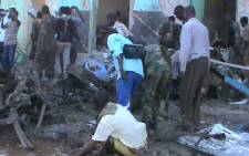 People and soldiers search in the rubble of a destroyed building on 28 February, 2016 in Baidoa after twin explosions in the Somali city killed at least 30 people. An initial car bomb struck a popular restaurant in a busy part of the regional capital on Sunday afternoon, with a suicide bomber nearby hitting people as they fled the area. The Al-Qaeda aligned Shebab jihadists claimed responsiblity for the attacks, saying local officials were targeted. Picture: AFP.