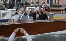 US actor George Clooney (R) waves to fans from a taxi boat on the Grand Canal on his way to the Aman hotel on 27 September 2014 in Venice, where Clooney and British fiancée, Amal Alamuddin celebrate their wedding. Picture: AFP/ANDREAS SOLARO